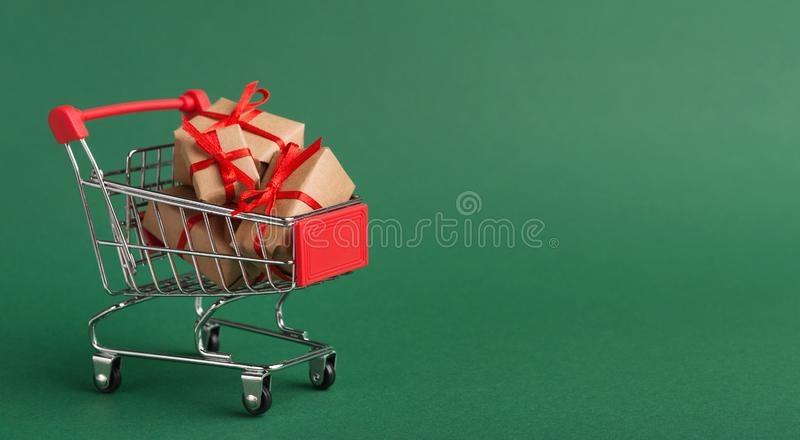 Shopping cart with craft Christmas gifts over green background stock photography
