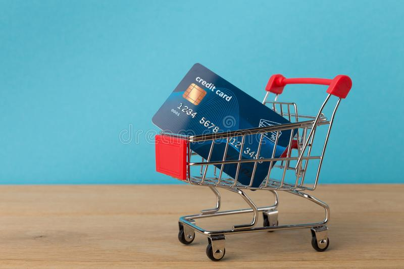 Shopping cart with credit card on blue background stock photography