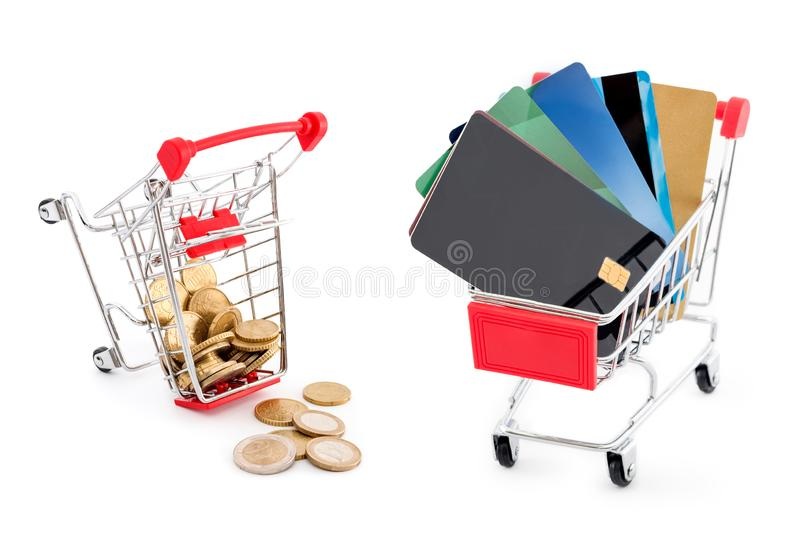 Shopping cart with credit cards and another cart full of euro coins falling from it on white background. Credit cards are winning. And cash is defeated. Old and stock photo