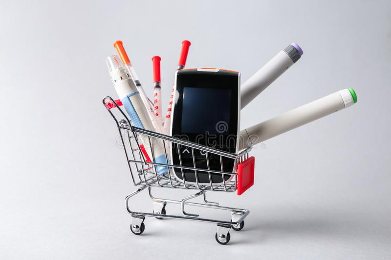 Shopping cart with digital glucometer, lancet pen and syringes on light background. Diabetes concept stock image