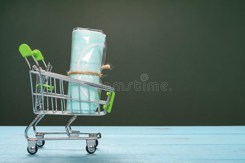 Shopping cart with disposable medical face mask concept of buying masks and respirators stock photography