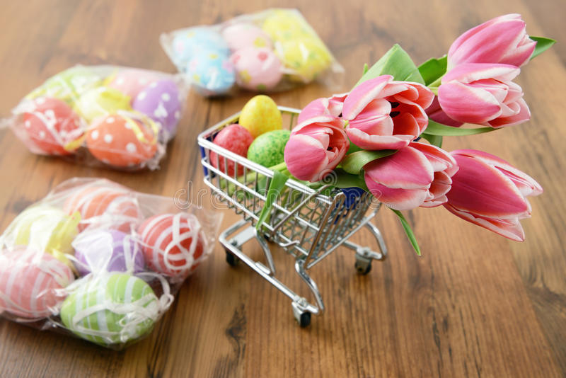 Shopping cart with easter items like bunch of tulips and eggs. royalty free stock photography