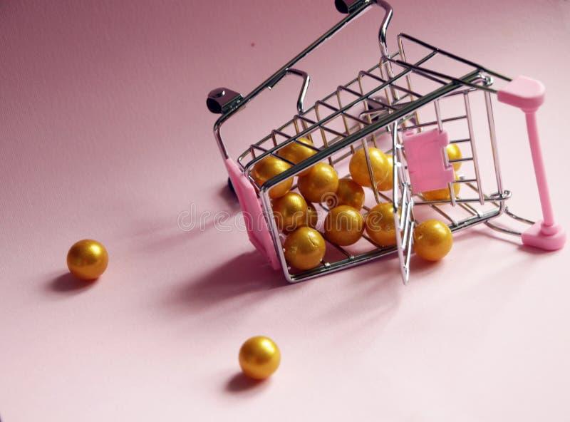 Shopping cart. Fallen Supermarket trolley full of golden balls on pink background. Consumerism concept photo. Shopping cart. Fallen Supermarket trolley full of stock photos