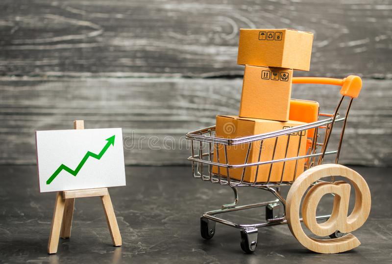 Shopping cart filled with boxes, email symbol and stand with green up arrow. shopping online. Growth rate of Internet sales. Advertising services. E-commerce stock images