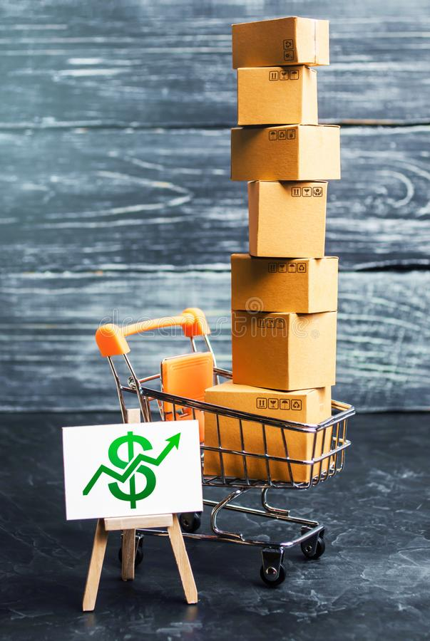 Shopping cart filled with boxes and a stand sign with a green dollar up arrow. shopping online. development of Internet network. Trade. E-commerce. sales of stock image