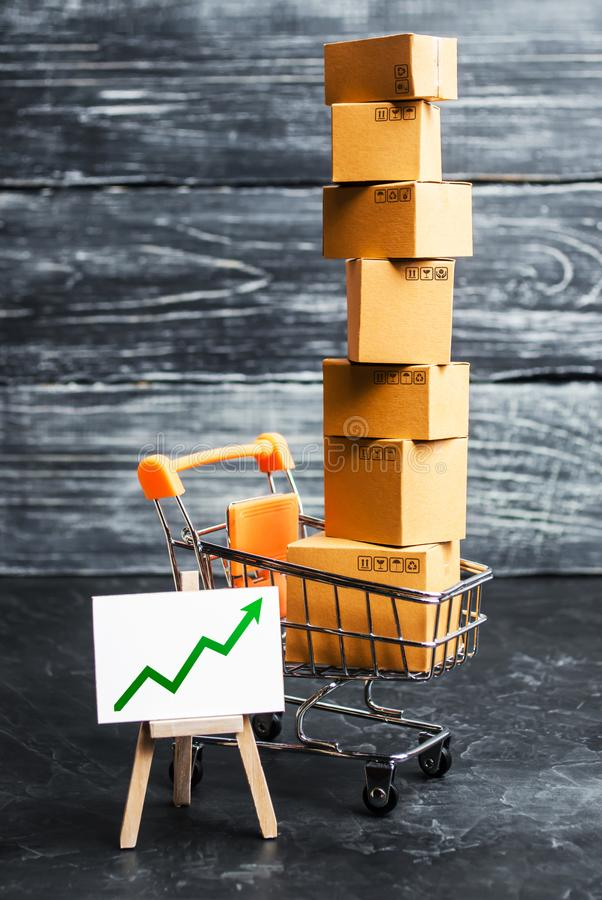 Shopping cart filled with boxes and a stand sign with a green up arrow. shopping online. development of Internet network trade. E-commerce. sales of goods and stock photos