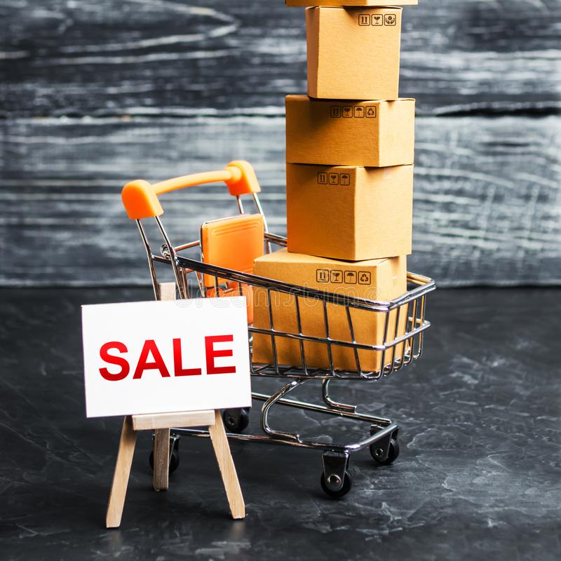 A shopping cart filled with cardboard boxes and an easel with the word Sale. Advertising sale, marketing. Business strategy. Analysis. Discount. Shopping online stock image