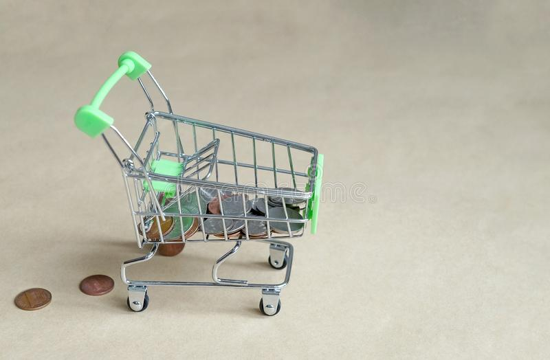 Shopping cart filled with coins, lost money from the basket. Metal shopping trolley is filled with coins, money is lost from the basket, the concept of expensive royalty free stock image