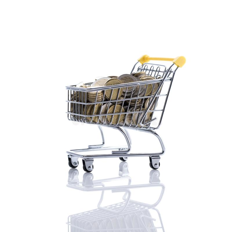 Shopping cart filled with currency. Supermarket shopping cart full of money on white background: retail, price and savings concept royalty free stock image
