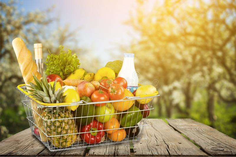 Shopping cart filled with various groceries in. Shopping cart full green background colorful bag stock photos