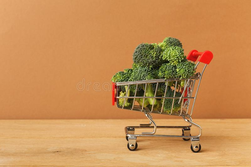 Shopping cart full of broccoli. On wooden background, side view. Mockup for food products. Shopping, healthy eating concept royalty free stock images