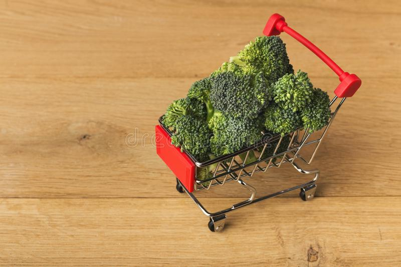 Shopping cart full of broccoli. On wooden background, top view. Mockup for food products. Shopping, healthy eating concept stock photos