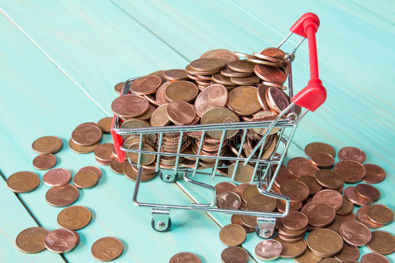 Shopping cart full of coins. Shopping cart full of Euro cent coins royalty free stock image
