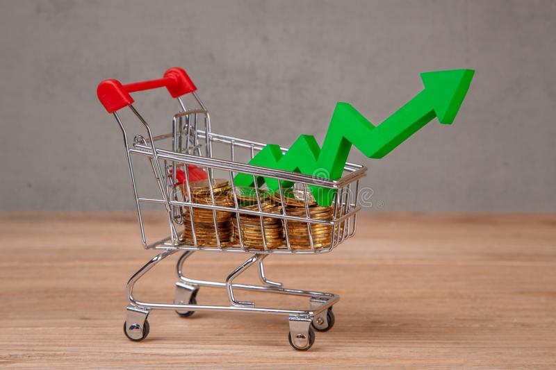 Shopping cart full of coins and green arrow up. Sales growth stock image