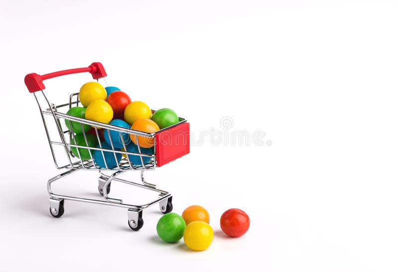 Shopping cart full of colorful candy dragee stock photo