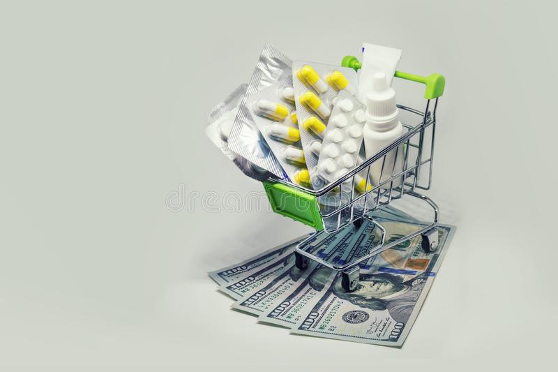 Shopping cart full of drug and medicine pills on dollar money. Pharmaceutical cost concept. medications in the cart. buying medicines royalty free stock images