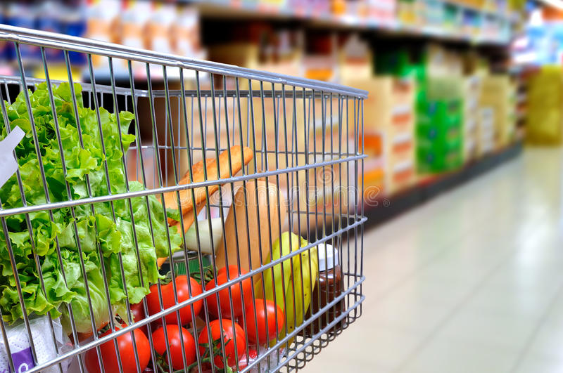 Shopping cart full of food in supermarket aisle side tilt. Shopping cart full of food in the supermarket aisle. Side tilt view. Horizontal composition stock image