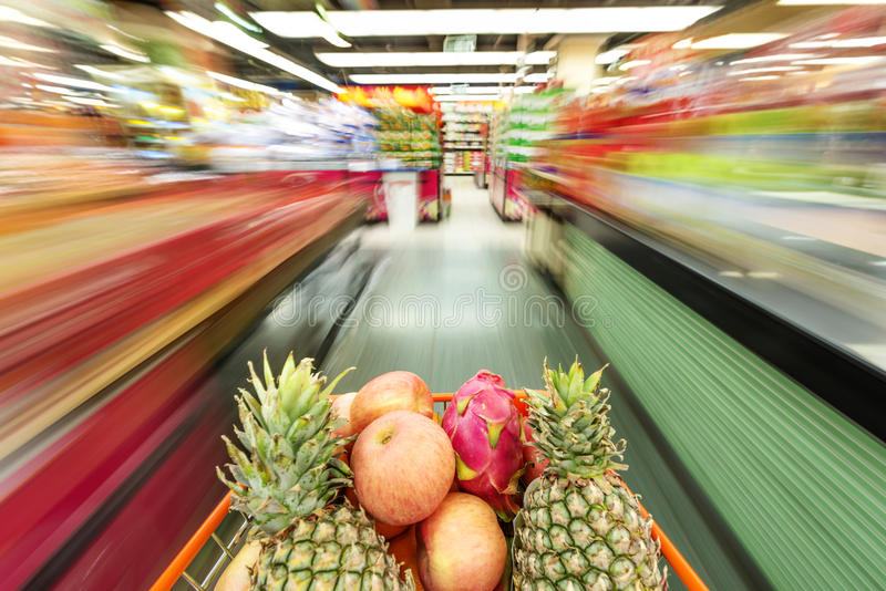 A shopping cart full of fruit on store shelves. Supermarket interior, filled with the fruit of the shopping cart stock images