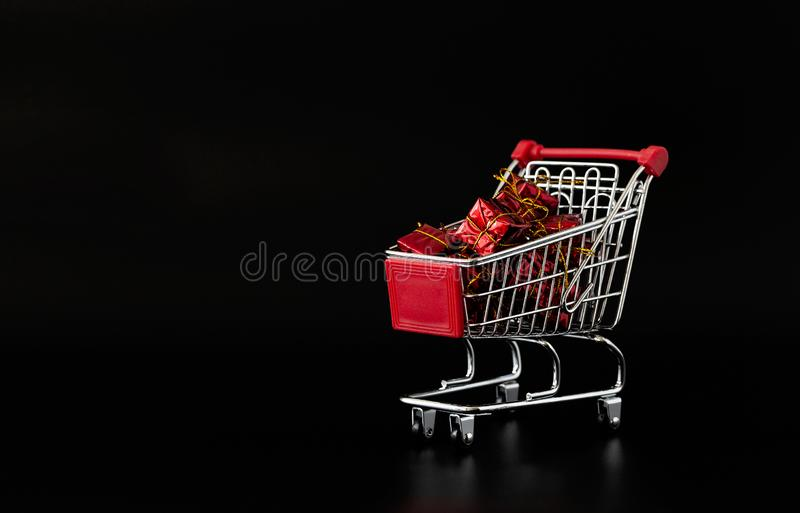 Shopping cart full of gifts. Shopping cart on black background. Minimalist style. Creative design. Copy space. Sale. Discount, shopaholism concept royalty free stock images