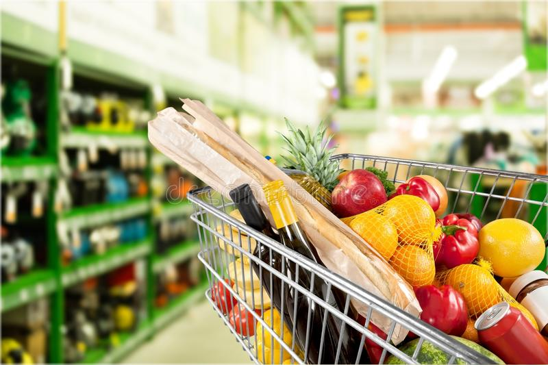 Shopping cart filled with various groceries in. Shopping cart full green background colorful bag stock images
