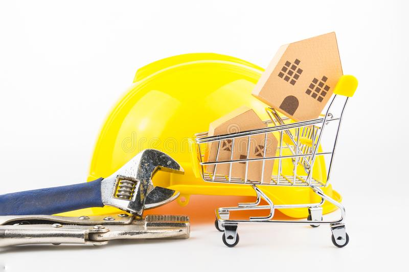 Shopping cart full of paper hose model and construction tools, i. Solated on white background with copy space.Real estate concept, New house concept, Repair royalty free stock image