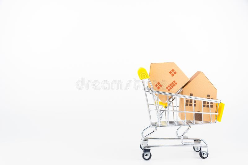 Shopping cart full of paper hose model, isolated on white background with copy space.Real estate concept, New house. Concept.Buying a house royalty free stock photography