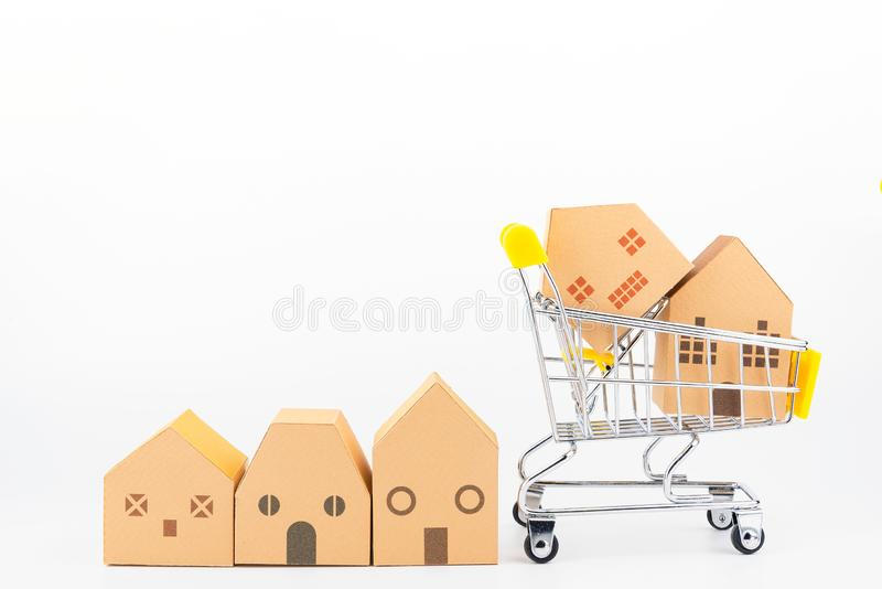 Shopping cart full of paper hose model, isolated on white background with copy space.Real estate concept, New house. Concept.Buying a house royalty free stock photo