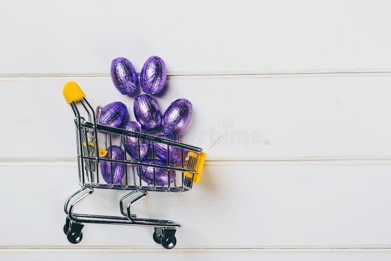 Shopping cart full of violet easter eggs, on white backgdrop, copy space. Shopping cart full of violet easter eggs, on the white backgdrop, copy space stock photography
