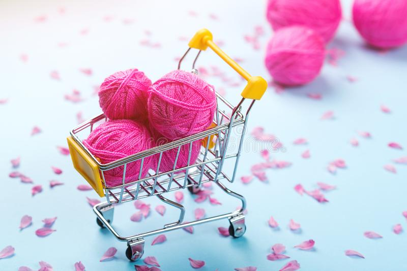Shopping cart full of wool knitting balls. Knitting background. Pink wool yarns. Colorful pink threads on blue paper background. stock image