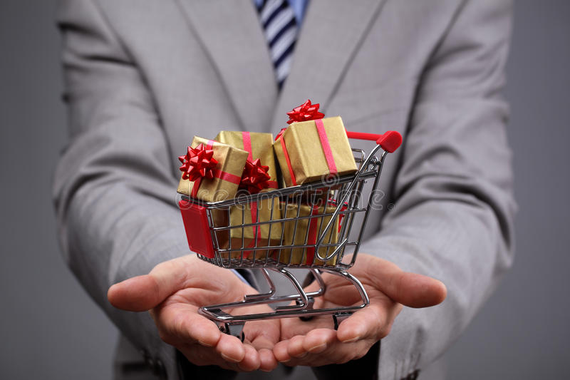 Shopping cart with gift box. Businessman with shopping cart full of gift boxes concept for gift shopping, business gift, christmas or valentine's day gift stock images