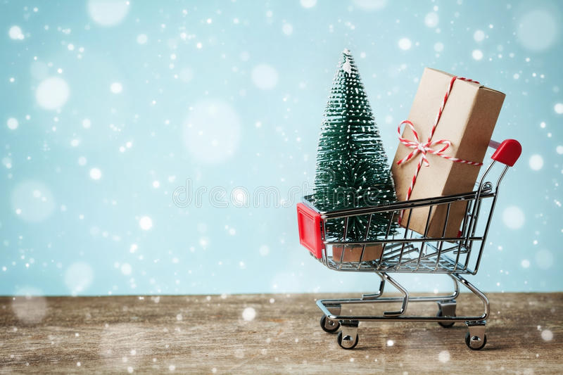 Shopping cart with gift or present and fir tree on snowy effect background. Christmas and New year sale concept. Greeting card. royalty free stock photography