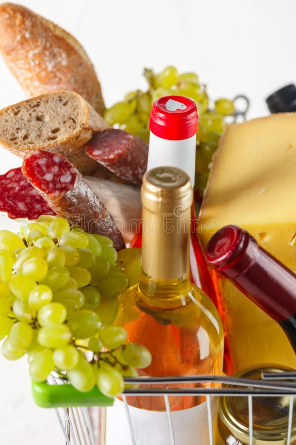 Shopping cart with groceries. Salami, grapes, bread, cheese and wine. Products in the basket. Salami, grapes, bread, cheese and wine closeup on white background stock photo