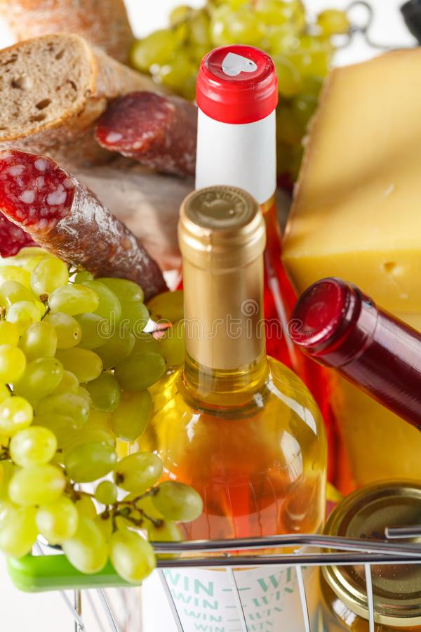 Shopping cart with groceries. Salami, grapes, bread, cheese and wine. Products in the basket. Salami, grapes, bread, cheese and wine closeup stock photos