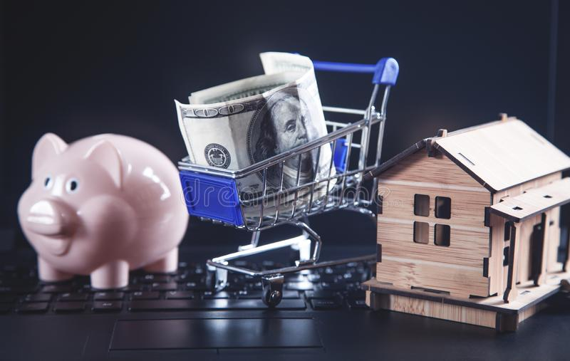 Shopping cart with house model on laptop keyboard royalty free stock photography