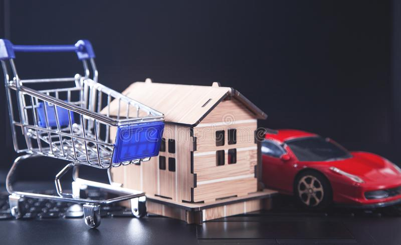 Shopping cart with house model on laptop keyboard royalty free stock image