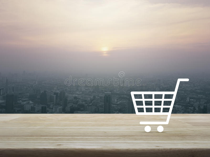 Shopping cart icon on wooden table over aerial view of cityscape at sunset, vintage style, Shop online concept royalty free stock images