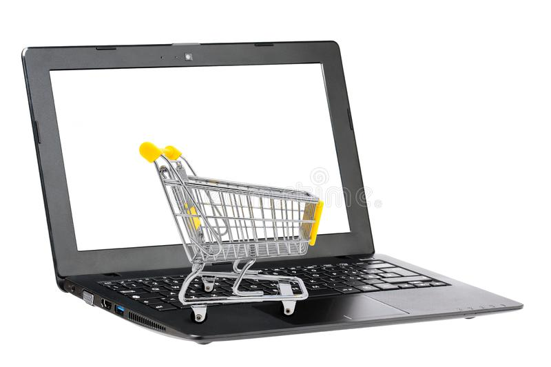 Shopping cart on keyboard of blank screen black laptop isolated on white. Electronic commerce concept royalty free stock image