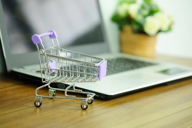 Shopping cart and laptop computer, Concepts online shopping where consumers can buy products directly. From home or work stock photo