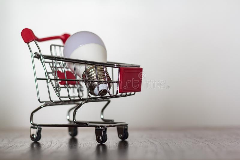 Shopping cart with led lamp on wooden table royalty free stock image