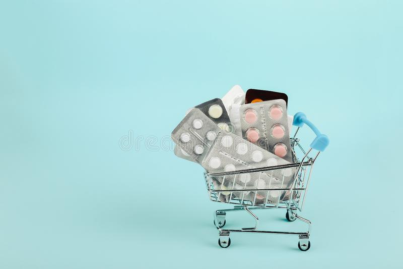 Shopping cart loaded with pills on a blue background. The concept of medicine and the sale of drugs. Copy space. Shopping cart loaded with pills on blue stock images