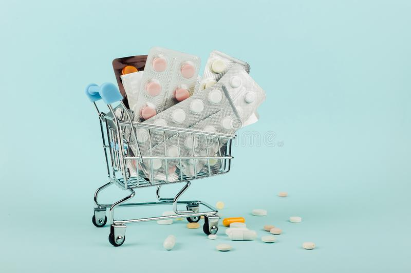 Shopping cart loaded with pills on a blue background. The concept of medicine and the sale of drugs. Copy space. Shopping cart loaded with pills on blue stock photography