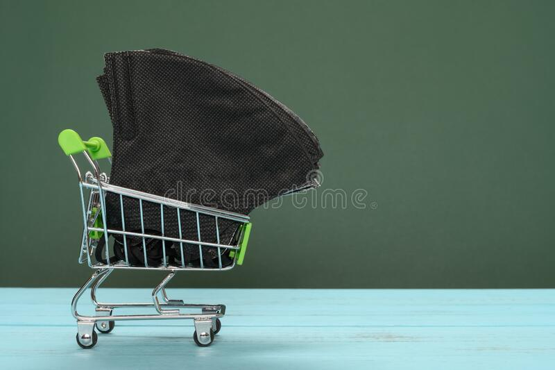 Shopping cart with medical face masks concept of buying masks and respirators stock image
