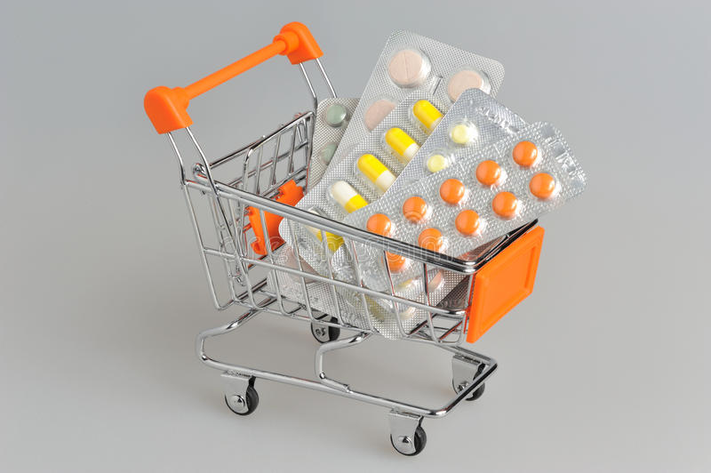 Shopping cart with medical supplies on gray. Background stock photo