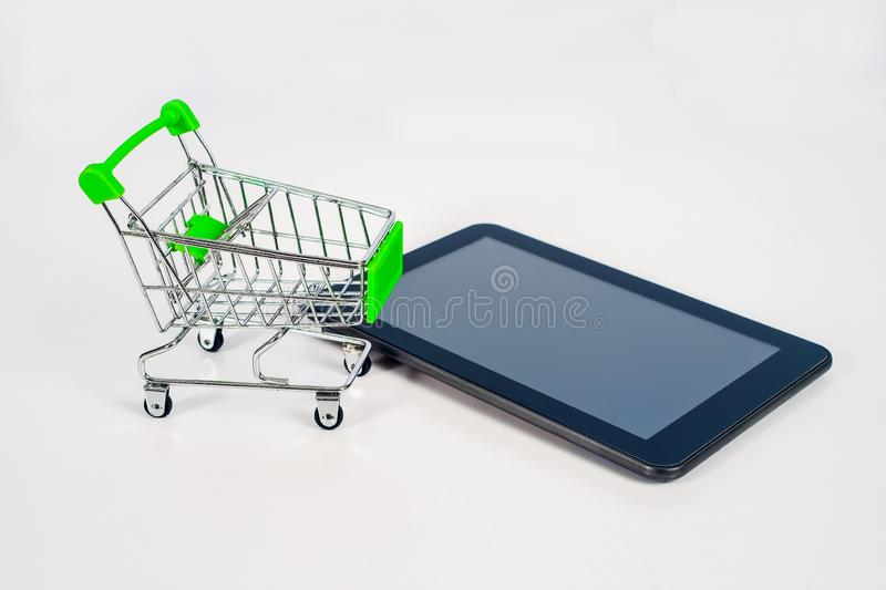 Shopping cart or metal trolley on mobile tablet for Online shopping. And ecommerce stock images
