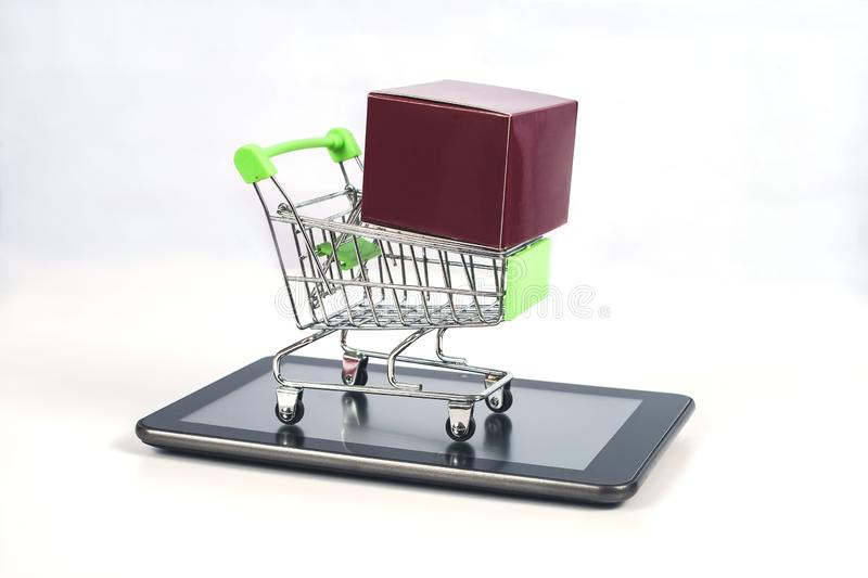 Shopping cart or metal trolley on mobile tablet for Online shopping. And ecommerce stock photo