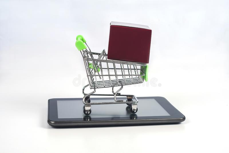 Shopping cart or metal trolley on mobile tablet for Online shopping. And ecommerce royalty free stock images