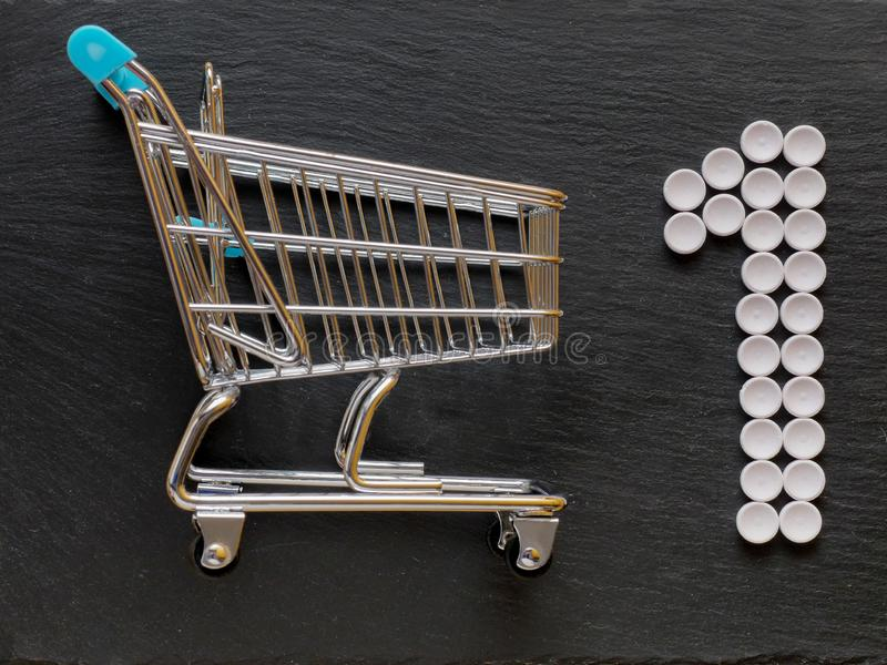 Shopping cart and number one sign made from medical pills, Concept healthcare priority and shopping royalty free stock image