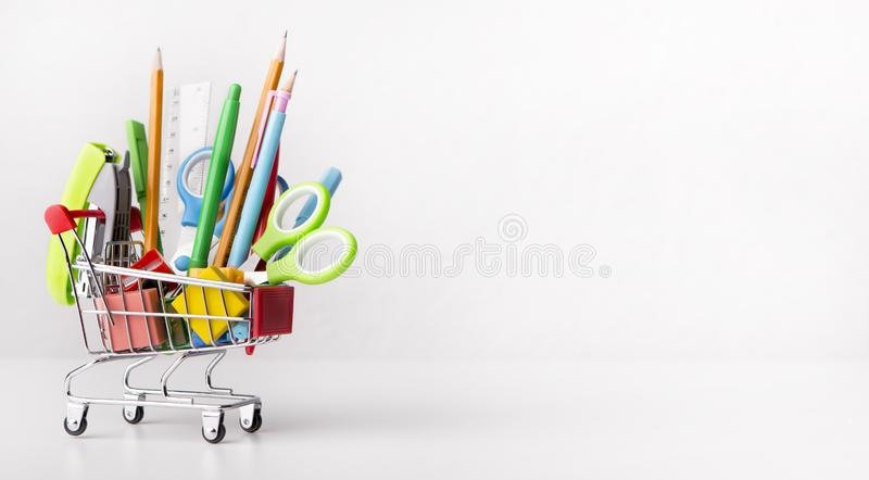Shopping cart with office stationery isolated on white. Sale of supplies. Shopping cart with office stationery isolated on white background with copy space for royalty free stock image