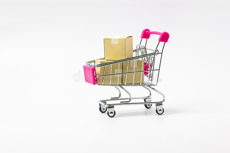 Shopping cart with paper cartons on white background. stock photography