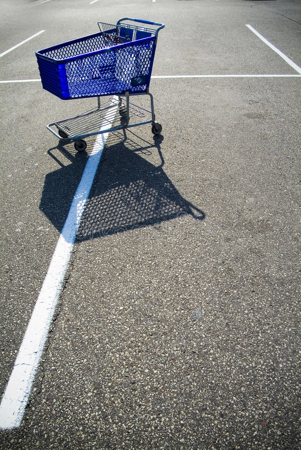 Shopping cart in parking lot stock images